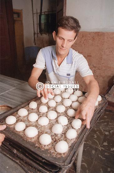 Baker placing bread rolls onto tray in bakery in Havana; Cuba,
