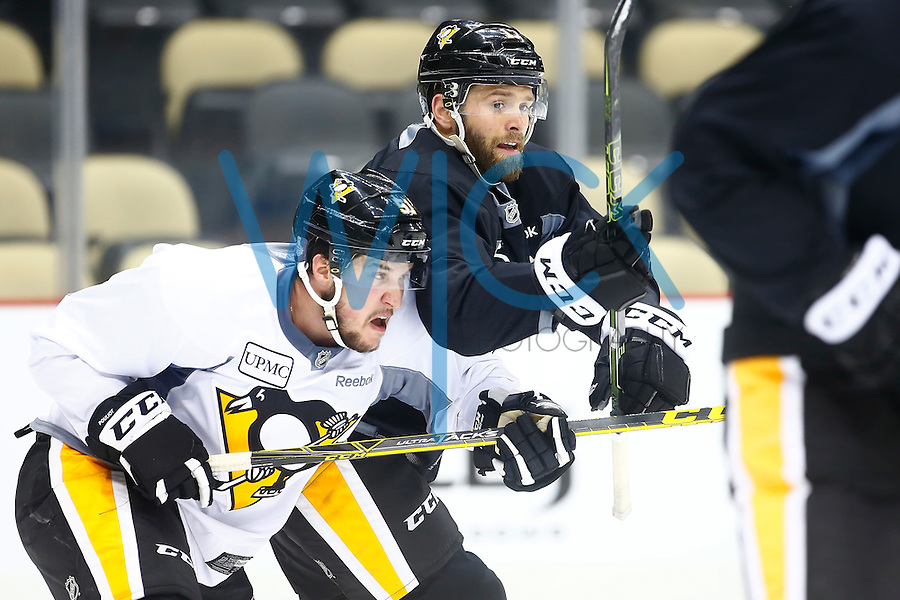 Bryan Rust #17 and Derrick Pouliot #51 of the Pittsburgh Penguins jostle for position during practice prior to the start of the Stanley Cup Final series between the Pittsburgh Penguins and the San Jose Sharks at Consol Energy Center in Pittsburgh, Pennslyvania on May 29, 2016. (Photo by Jared Wickerham / DKPS)