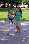 Motherhood.  Mom and daughter play on swing