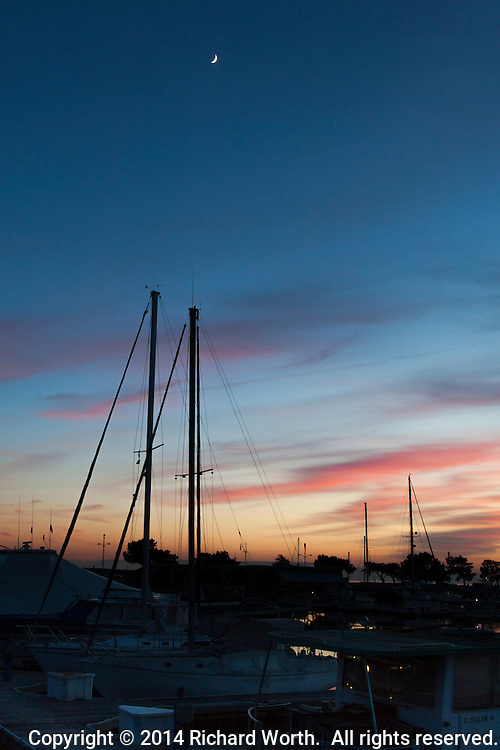 A waxing crescent moon floats high in a sunset painted sky above the masts of boats moored at the San Leandro Marina on San Francisco Bay.