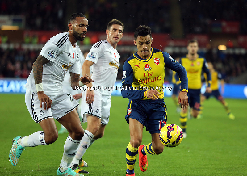 Sunday 09 November 2014 <br /> Alexis Sanchez of Arsenal (R) is closely marked by Kyle Bartley of Swansea<br /> Barclays Premier League, Swansea City FC v Arsenal City at the Liberty Stadium, Swansea, Great Britain. EPA/Dimitris Legakis