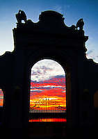 A spectacular orange and red sunset reflecting in the pool and seen through the wrought-iron gates and arch of the Natatorium War Memorial, a historical site on Waikiki Beach, opposite Kapiolani Park.