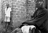 An orphaned boy watches a neighbour with an infant in Kampala, Uganda on April 17, 2001. More than 13 million African children who have been orphaned by the the AIDS pandemic. Worldwide, more than 20 million people have died since the first cases of AIDS were identified in 1981.