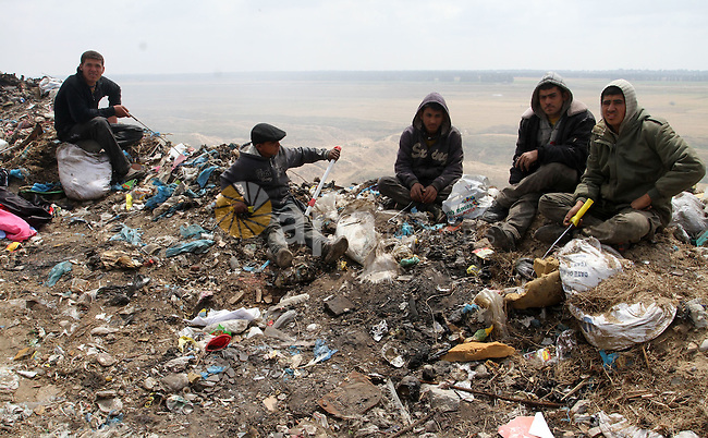 Palestinian workers get a rest on the garbage near the border with Israel, east of Rafah town, in the southern Gaza Strip, April 16, 2015. Workers collect the household recyclables, metals and plastic from landfill and garbage to sell to the Israeli and local factories. Photo by Abed Rahim Khatib
