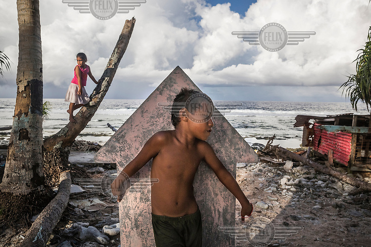 Children playing 'hide and seek' in Teone's graveyard. Massive coastal erosion in Teone caused many coconut trees fall down, and the sea eaten its way into and around the trees that are still standing. People from Teone are threatened on one side by the ocean and its tide surges and on the other by a pit that fills with salt water at high tide due the soil salinisation.