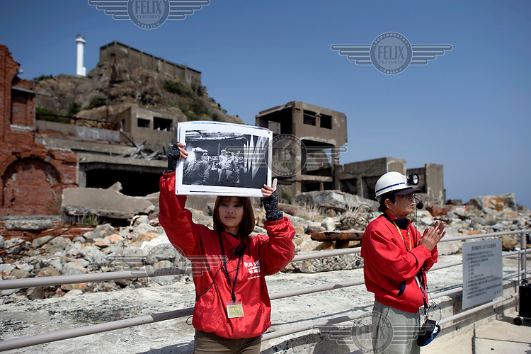 Guides on Hashima Island, nicknamed Gunkanjima or Battleship Island as it resembles a massive battleship. It is now an abandoned cluster of buildings rising in the Pacific ocean.<br /> From 1887 until 1974, the small island was a coal mine for the Mitsubishi Mining Company with 5259 residents, resulting as the highest population density in ever recorded worldwide. In 1974, the mine was closed, and its residents had to leave Gunkanjima, abandoning the island with all its buildings. The island was a location for the James Bond film Skyfall. /Felix Features