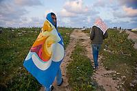 Immigrati clandestini vagano nell'isola di Lampedusa dopo aver passato la notte all'aperto.