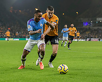 27th December 2019; Molineux Stadium, Wolverhampton, West Midlands, England; English Premier League, Wolverhampton Wanderers versus Manchester City; Raheem Sterling of Manchester City with the ball at his feet being held back by Conor Coady of Wolverhampton Wanderers  - Strictly Editorial Use Only. No use with unauthorized audio, video, data, fixture lists, club/league logos or 'live' services. Online in-match use limited to 120 images, no video emulation. No use in betting, games or single club/league/player publications