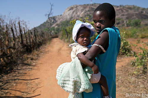 Liliosa, 16, carries her baby to her home in Masvingo Province, Zimbabwe. She forages for food in the wild for her, her baby and her young sister, who is born HIV positive. <br /> <br /> Drought in southern Africa is devastating communities in Zimbabwe, leaving 4 million people urgently in need of food aid. The government declared a state of emergency,. <br /> <br /> Here in Masvingo Province, the country's hardest hit province, vegetation has wilted, livestock is dying, and people are at serious risk of famine. <br /> <br /> Pictures shot by Justin Jin