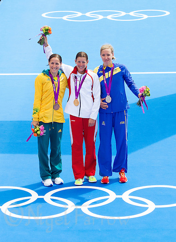 04 AUG 2012 - LONDON, GBR - Nicola Spirig (SUI) of Switzerland (centre) poses with her gold medal, after winning the London 2012 Olympic Games women's Triathlon in Hyde Park, London, Great Britain, flanked by bronze medalist Erin Densham (AUS) of Australia  (left) and silver medalist Lisa Norden (SWE) of Sweden (right) .(PHOTO (C) 2012 NIGEL FARROW)