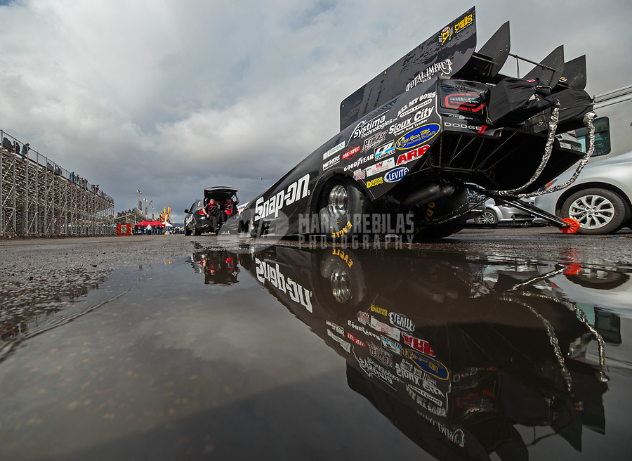 Feb 22, 2019; Chandler, AZ, USA; The car of NHRA funny car driver Cruz Pedregon reflects in a rain puddle as the car is towed to the staging lanes during qualifying for the Arizona Nationals at Wild Horse Pass Motorsports Park. Mandatory Credit: Mark J. Rebilas-USA TODAY Sports