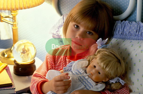 sad looking young girl sick in bed taking temperature of doll with oral thermometer