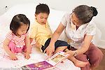 18 month old toddler girl and 3 year old boy with grandmother looking at book interaction