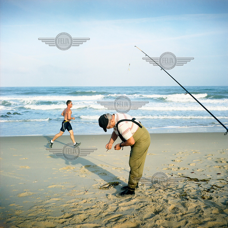 A fisherman and a man run on the beach at Lacanau-Ocean, a resort along the Cote d'Argent on the Atlantic ocean.