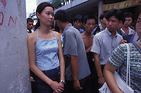 Men pass a women in Guangzhou railway station. An average gender inbalance 118 males to 100 females caused by the strict One Child Policy and the preference for boys means that there is a shortage of women in China.
