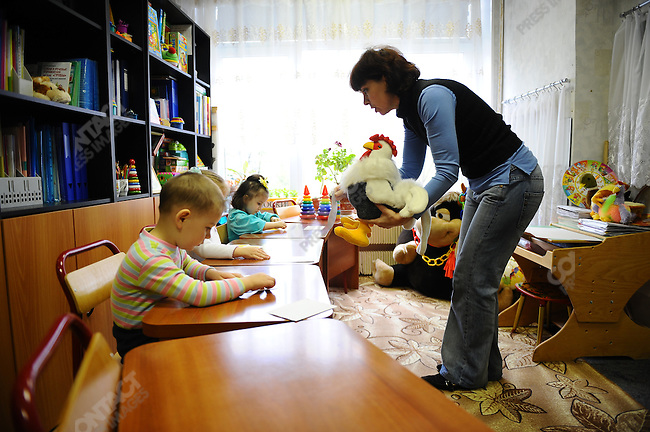 At Orphanage No.11 in Moscow a teacher worked with children in a small class of three. Russia, April 23, 2010