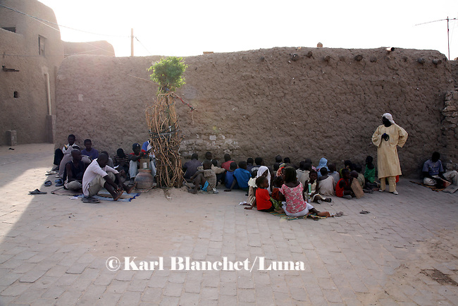 "The pupils learn Coran in front of the house of the marabout in the old area of Timbuctu, Mali, called ""medina"". The pupils learn coranic versets written on wooden boards. The coranic schools in Timbuctu are only open early in the morning and on Saturdays in order to allow pupils to attend the public school."