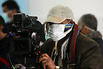 A Palestinian cameraman wears a protective mask as he works in Gaza city on Dec 8,2009. Two Palestinian women have died of A/ H1N1 virus in Gaza Strip, the first deaths from the virus in the Israeli-blockaded enclave, a health official said Monday. Photo by Wissam Nassar