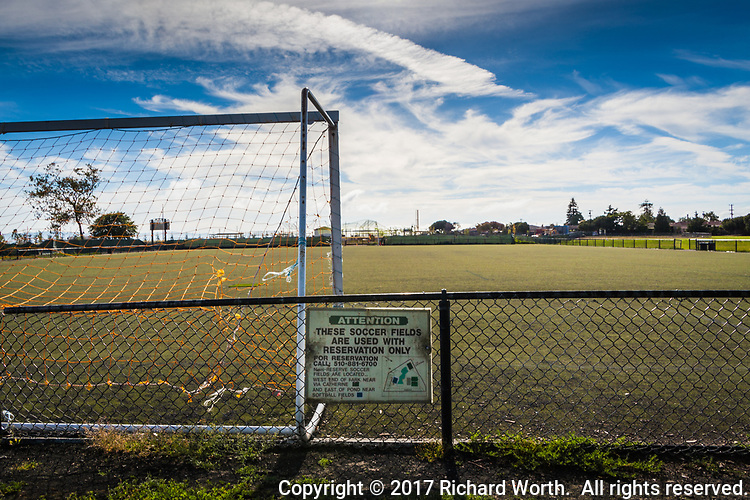 A soccer goal and groomed soccer fields stretch beyond a fence with a sign advising These Fields are Reservation Only.
