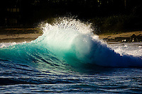 Small wave illuminated from afternoon sun as backwash collides with oncoming wave at Makaha beach on Oahu, Hawaii
