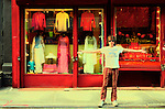 Man on the streets of the East Village in front of a clothing shop extending his arms. Manhattan, New York City.