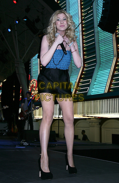 EMILY WEST .Performs at ACM Weekend at the Freemont Street Experience, Las Vegas, Nevada, USA,16th April 2010..full length music concert gig live on stage black shoes heels shorts blue top ruffles ruffle necklace microphone strapless .CAP/ADM/MJT.© MJT/AdMedia/Capital Pictures.