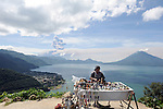 iew of the eruption of Fuego Volcano in Guatemala from San Jorge La Laguna, Solola, one of the villages by Lake Atitlan, in the morning hours. A woman sells crafts at a roadside stall overlooking the lake.