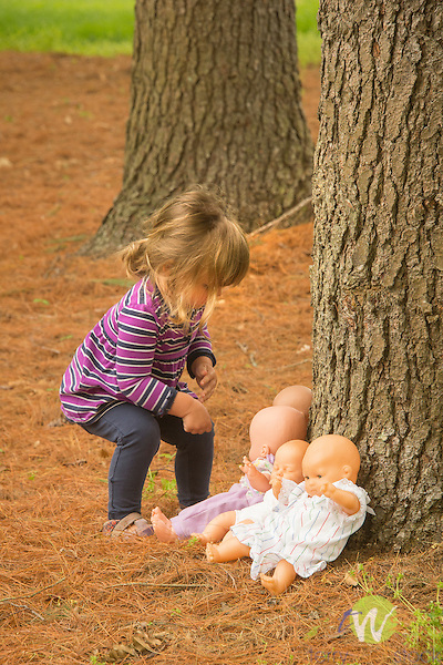 Toddler playing with four doll babies under pine tree.