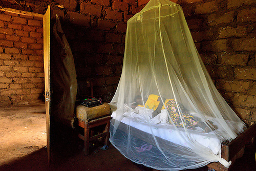 In a rural village in northeast Rwanda, a mother and her new born nap under their bed net.