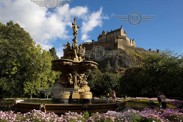 Edinburgh Castle looms over a fountain in Princes Street Gardens.