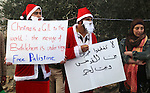 Palestinian protesters dressed in Father Christmas costumes take part in a demonstration against the Israeli settlements and demanding for free movement for the Palestinians during the Christmas period near a checkpoint in the West Bank biblical city of Bethlehem on December 23, 2014. Photo by Muhesen Amren