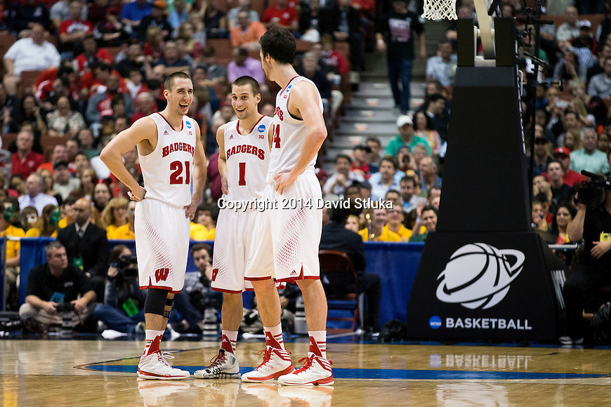 Wisconsin Badgers teammates Josh Gasser (21), Ben Brust (1) and Frank Kaminsky (44) share a moment late in the game during the fourth-round game in the NCAA college basketball tournament against the Baylor Bears Thursday, March 27, 2014 in Anaheim, California. The Badgers won 69-52. (Photo by David Stluka)