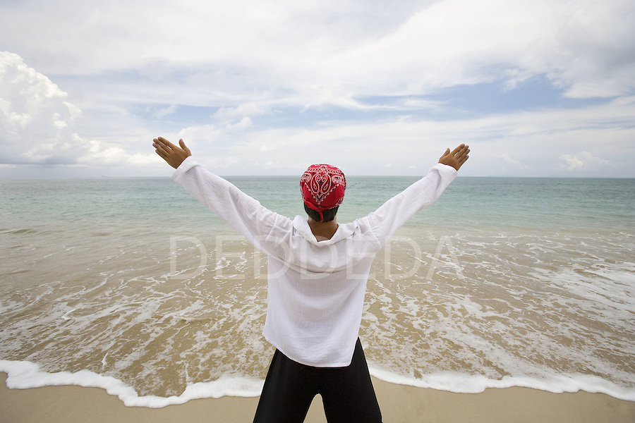 A man in a white shirt and red bandana stretches at a beach in Koh Lanta, Thailand.