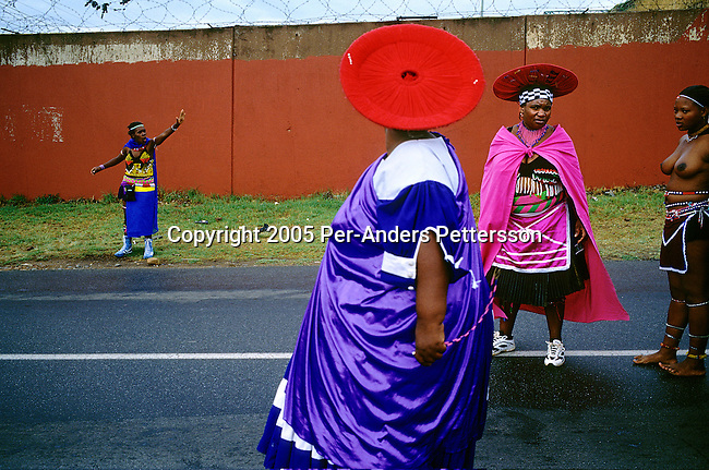 SOWETO, SOUTH AFRICA MARCH 8: Unidentified Zulu women dressed in traditional clothing stop the traffic as they are marching with about fifty virgins on a road on March 8, 2005 in Soweto, Johannesburg, South Africa. This to celebrate their virginity. The girls were earlier in the day checked if they were virgins or not. Soweto is South Africa?s largest township and it was founded about one hundred years to make housing available for black people south west of downtown Johannesburg. The estimated population is between 2-3 million. Many key events during the Apartheid struggle unfolded here, and the most known is the student uprisings in June 1976, where thousands of students took to the streets to protest after being forced to study the Afrikaans language at school. Soweto today is a mix of old housing and newly constructed townhouses. A new hungry black middle-class is growing steadily. Most residents work in Johannesburg but the last years many shopping malls has been built, and people are starting to spend their money in Soweto.  .(Photo by Per-Anders Pettersson/Getty Images).