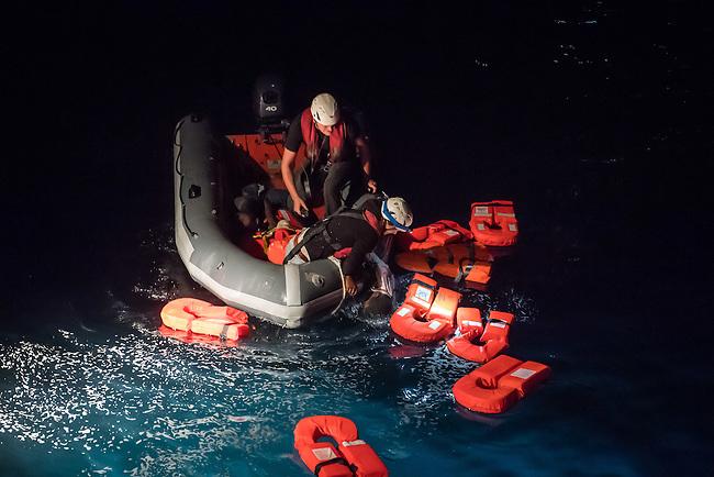 Die Sea Watch-2 Crew war am Freitag den 21. Oktober 2016 in den fruehen Morgenstunden waehrend ihrer 13. SAR-Mission vor der libyschen Kueste zu einer Position ausserhalb der 12 Meilenzone gerufen worden. Es war ein Fluechtlingsschlauchboot gesichtet worden. Als die Sea Watch-2 dort eintraf sah sie ca. 150 Menschen zusammengepfercht in einem ueberfuellten Schlauchboot sitzen. Eine Versorgung der Menschen auf dem Fluechtlingsschlauchboot mit Rettungswesten durch die Rettungs Boote der Sea Watch-2 wurde von der libyschen Kuestenwache unterbunden. Ein Soldat der Kuestenwache enterte das Schlauchboot vom Bug und machte sich dann an dem Aussenbordmotor zu schaffen. Auf dem Weg dahin schlug und trat er die Gefluechteten ein. Nach einigen Minuten entfernte sich das Boot der Kuestenwache. Dann verlor der Bug des Schlauchbootes seine Luft und es brach Panik bei den Gefluechteten aus. Sie sprangen in das Wasser und versuchten zum Schiff Sea Watch-2 zu gelangen. Die Crew warf ihnen Schwimmwesten und Rettungsringe zu, die Besatzungen der Rettungsboote der Sea Watch-2 zogen Menschen aus dem Meer, dennoch sind bis zu 30 Menschen ertrunken. Vier Ertrunkene konnten von der Sea Watch geborgen werden.<br /> Im Bild: Mitglieder der Sea Watch-Crew bergen einen leblosen Koerper.<br /> 21.10.2016, Mediterranean Sea<br /> Copyright: Christian-Ditsch.de<br /> [Inhaltsveraendernde Manipulation des Fotos nur nach ausdruecklicher Genehmigung des Fotografen. Vereinbarungen ueber Abtretung von Persoenlichkeitsrechten/Model Release der abgebildeten Person/Personen liegen nicht vor. NO MODEL RELEASE! Nur fuer Redaktionelle Zwecke. Don't publish without copyright Christian-Ditsch.de, Veroeffentlichung nur mit Fotografennennung, sowie gegen Honorar, MwSt. und Beleg. Konto: I N G - D i B a, IBAN DE58500105175400192269, BIC INGDDEFFXXX, Kontakt: post@christian-ditsch.de<br /> Bei der Bearbeitung der Dateiinformationen darf die Urheberkennzeichnung in den EXIF- und  IPTC-Daten nicht entfernt werden, d