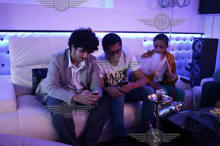 Three young men sit on a white leather sofa, looking at their phones and smoking a water pipe (hookah) in a coffee shop in Sana'a.