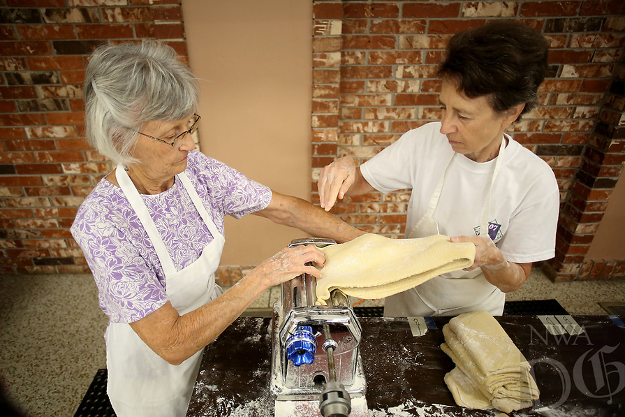 NWA Democrat-Gazette/DAVID GOTTSCHALK   Jeanette Burditt (left) and Gerrie Hughey roll out sheets of fresh pasta dough Monday, July 10, 2017, at the St. Joseph's Parish Hall in Tontitown. More than 3,000 pounds of pasta noodles are being prepared for the 119th Tontitown Grape Festival which runs Tuesday, August 1 thru Saturday August 5. The homemade spaghetti will be served August 3 thru Aug. 5. For more information see tontitowngrapefestival.com.