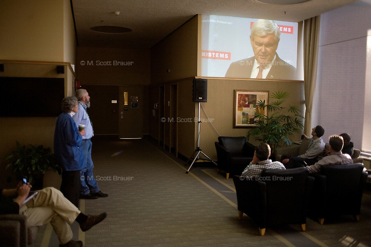 BAE Systems employees watch a live feed from an over-capacity room at the facility as Newt Gingrich speaks at campaign event at BAE Systems, a major defense contractor, in Nashua, New Hampshire, on Jan. 9, 2012.  Gingrich is seeking the 2012 Republican presidential nomination.