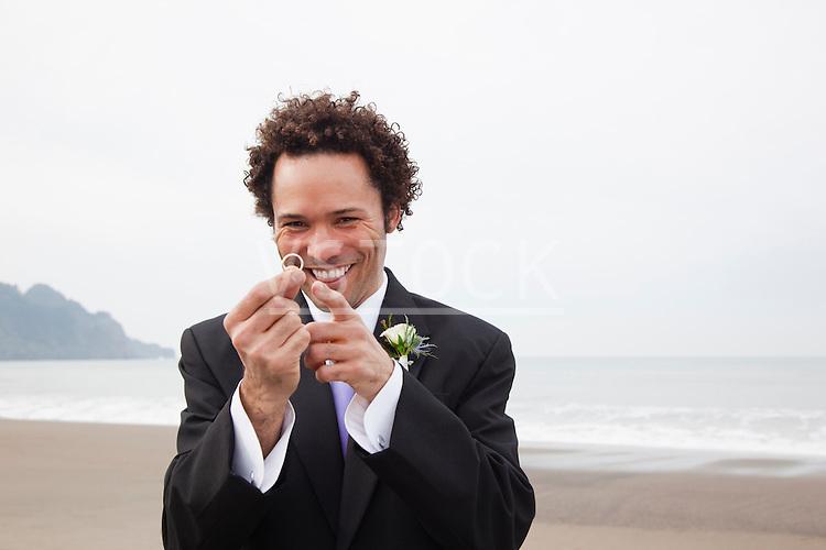 USA, California, San Francisco, Baker Beach, portrait of groom on beach holding ring