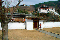A man walking through the grounds of the Ugyen Pelri Palace in Bhutan.  The Paro Dzong can be seen on the hill behind.