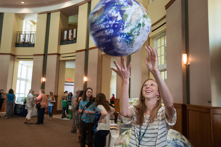 Megan Graver a Graduate student in the OU Office of Sustainability, tries to balance the globe on her finger during the Earth Day Reception.  Photo by Ohio University / Jonathan Adams