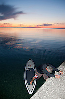A stand up paddleboard paddler steps onto his board off the Lake Superior breakwater at Grand Marais Michigan.