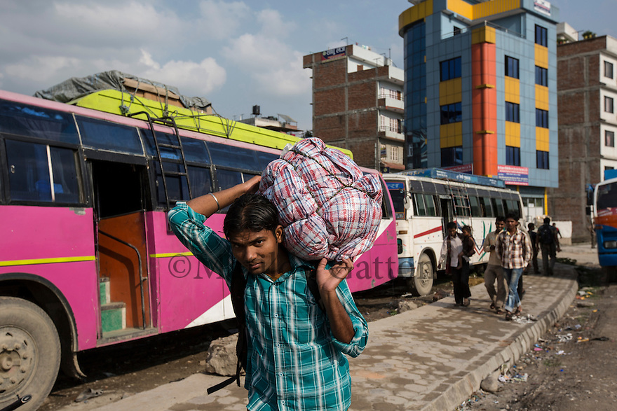"""Nepal - Kathmandu - Abodh Bandal, 22, arrives at the Gaushala bus station in Kathmandu in order to catch the bus which will take him back to his village of Prakomoha, in the Eastern district of Dhanusha. Bandal has just come back from Qatar, where he worked for four years as a construction worker. Although he was paid only 165 USD per month instead of the promised 220, he decided to stay in Qatar anyway in order to repay the 1,200-USD-loan he had taken. """"At the end of the day, I couldn't save much"""", he says honestly. Despite the disappointment, Bandal plans to return abroad soon to keep on maintaining his parents and sibling. """"This time I will try to go to Dubai"""" he says. """"I will never go back to Qatar again""""."""