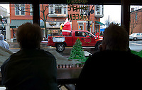 Bar patrons watchas an inflated Santa Claus in a truck passes in review at the Westerville, Ohio, annual Christmas parade arrives during a wet, rainy parade.  Photo Copyright Gary Gardiner. Not for reproduction without written permission.