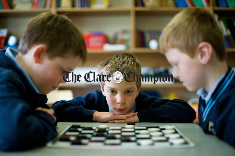 Jack Haverty, Ronan Tierney and Seadhna Liddy playing draughts at Ballycar National School. Photograph by John Kelly.