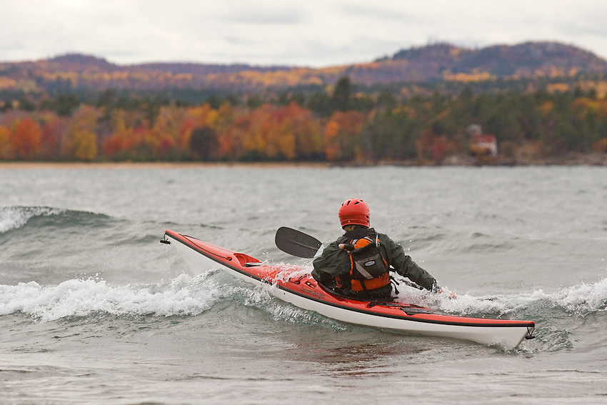 A sea kayaker in a red sea kayak paddles in rough conditions on Lake Superior near Marquette Michigan.