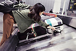 Woman picking up suitcase from airport baggage conveyor at Toronto Pearson International airport luggage claim, Canada