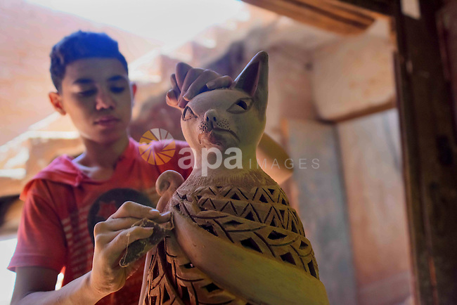 An Egyptian boy works at a pottery workshop in Cairo, on July 24, 2016. Pottery is an ancient and traditional craft in Egypt. Local workshops usually produce products such as bowls, pitchers, flower pots, and vases. Photo by Amr Sayed