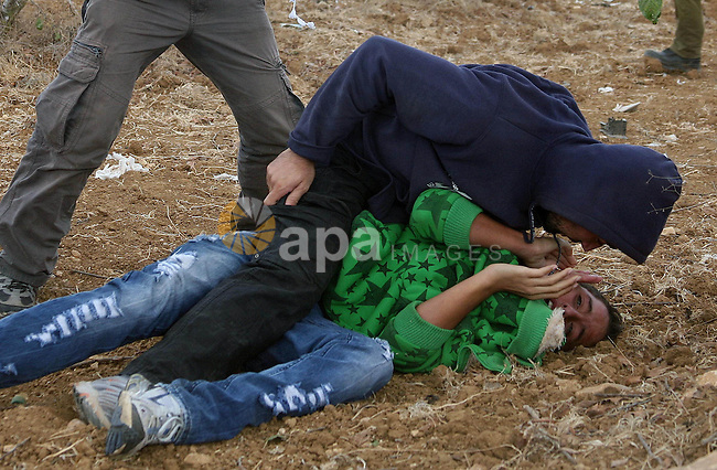 Israeli undercover forces arrest Palestinian boys during a demonstration by Palestinian, Israeli and foreign activists against the demolishing of farm land to be used in the construction of Jewish settlements near the existing Israeli settlement of Karmi Tsor near the Palestinian village of Beit Omar, just north of the West Bank town of Hebron on October 09, 2010 . Photo by Najeh Hashlamoun