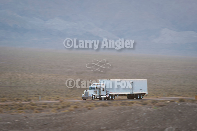 Loaded semi truck and trailer on Nevada's US Highway 95, morning.
